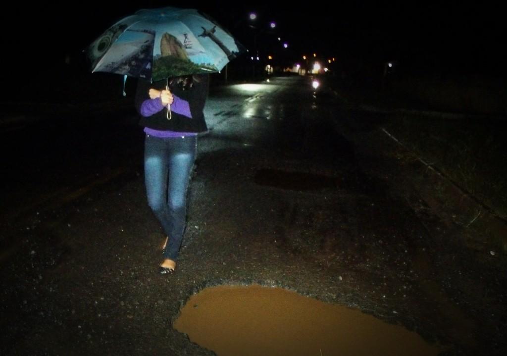 Pedestre caminha sob chuva fraca e desvia de buraco. (Foto: João Henrique | Maricá Info)