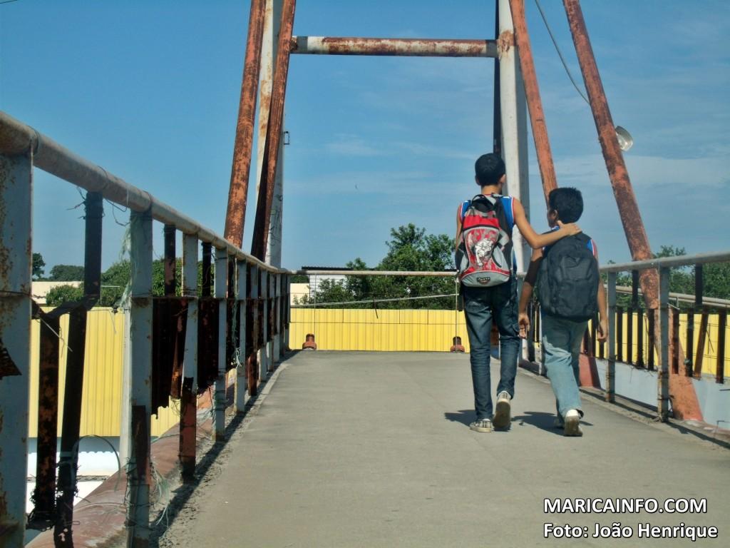 Crianças atravessam na passarela com guarda-corpos e estruturas comprometidas. (Foto: João Henrique | Maricá Info)