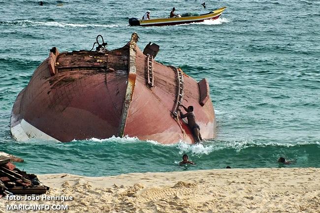 Banhistas desrespeitam isolamento e se arriscam subindo na embarcação naufragada. (fotos: João Henrique | Maricá Info)